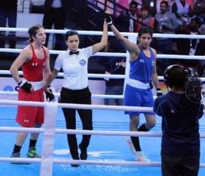 The referee raises Simranjeet Kaur's hand in victory